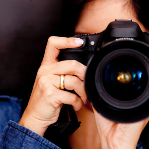 Portrait of a photographer covering her face with the camera