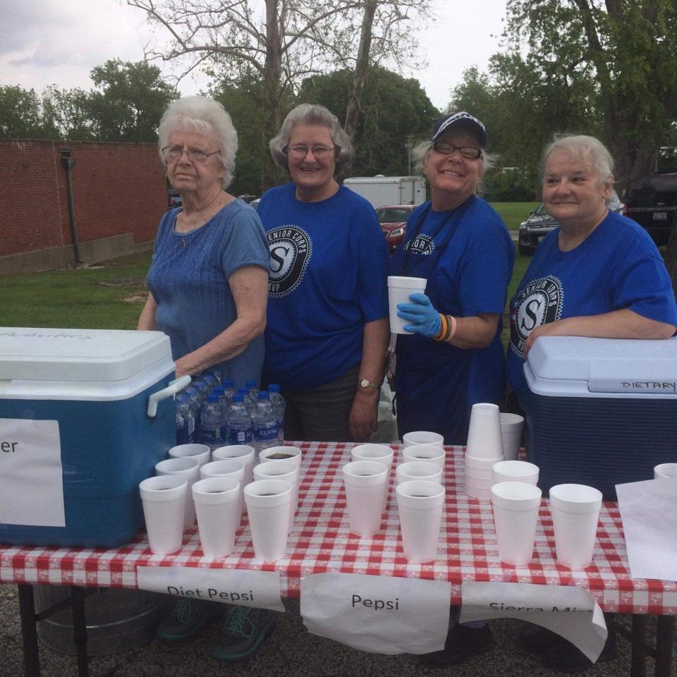 Various ladies serving soda in Styrofoam cups