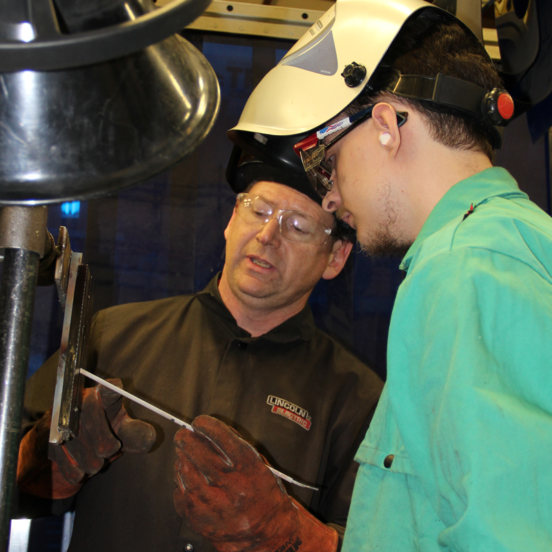 instructor teaching student to weld