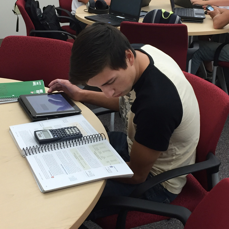 student looking at book while using tablet