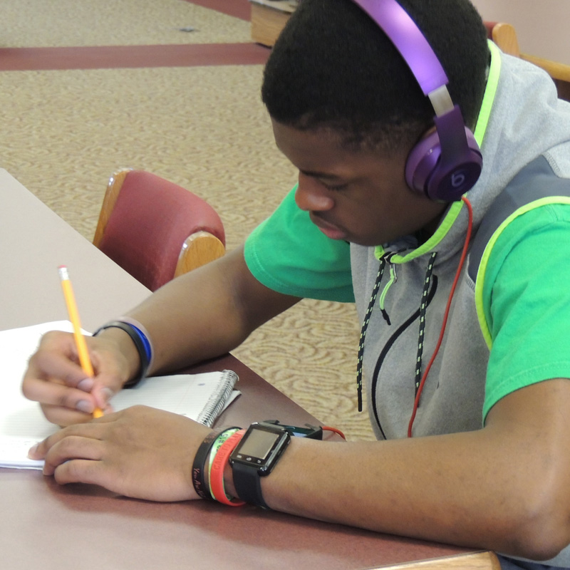 student with headphones on while writing in a notepad