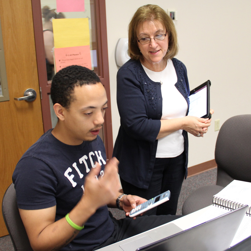 business instructor talking to student at a computer