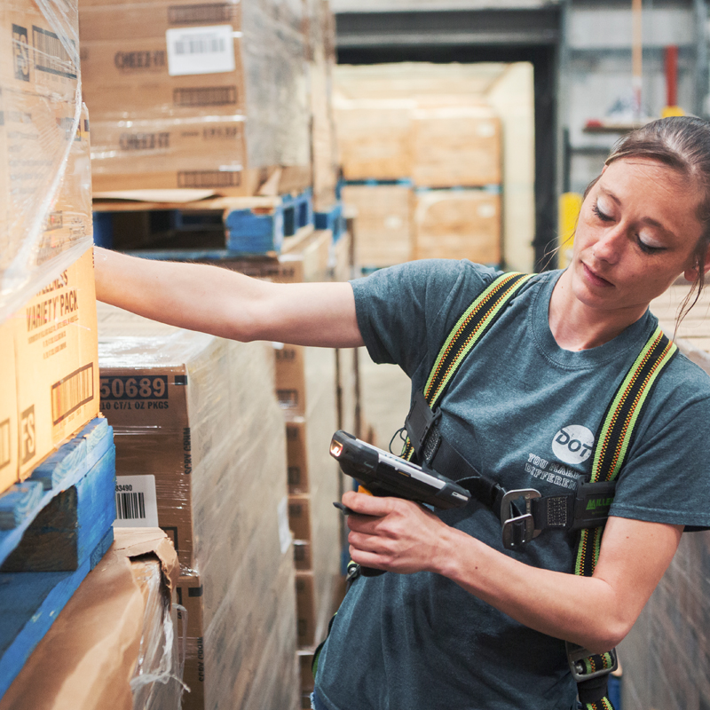 girl using a scanner to scan boxes at a warehouse