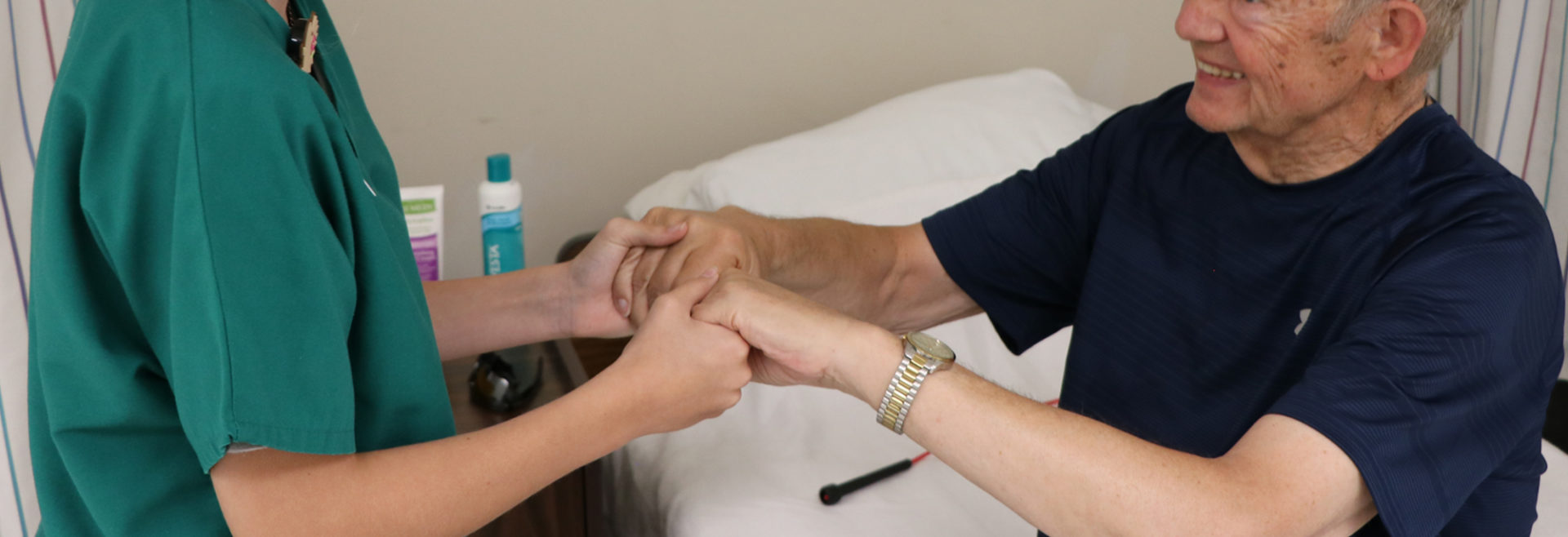 nursing student holding hands with a patient