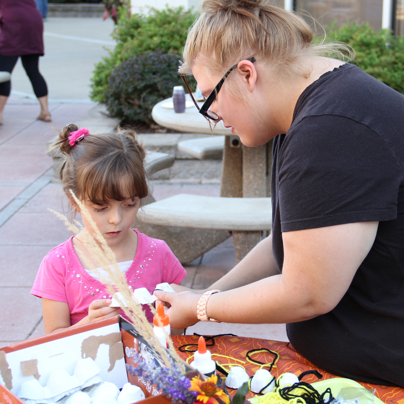 JWCC student making a craft with a young child