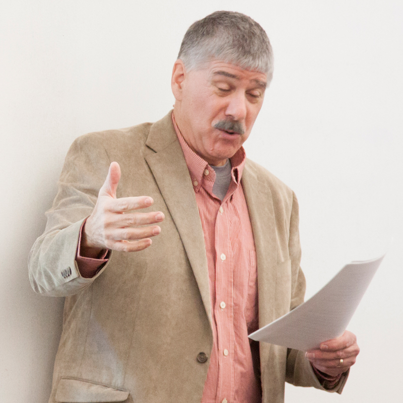 professor with papers in one hand and is talking