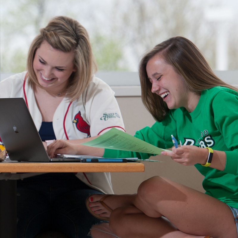 two girls smiling in front of a laptop