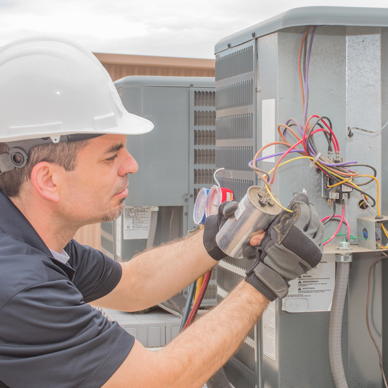 man connecting wires on a unit