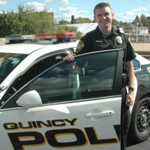 Quincy Police officer standing with car door open