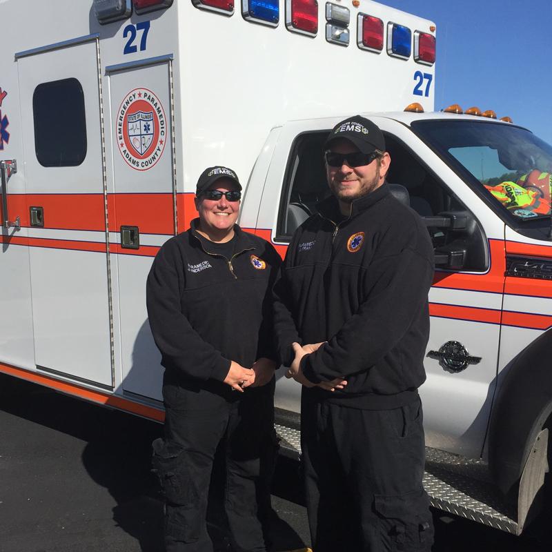 two paramedics standing next to the ambulance