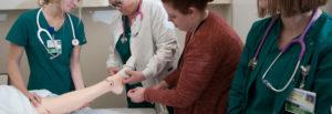student nurses watching as socks are put on