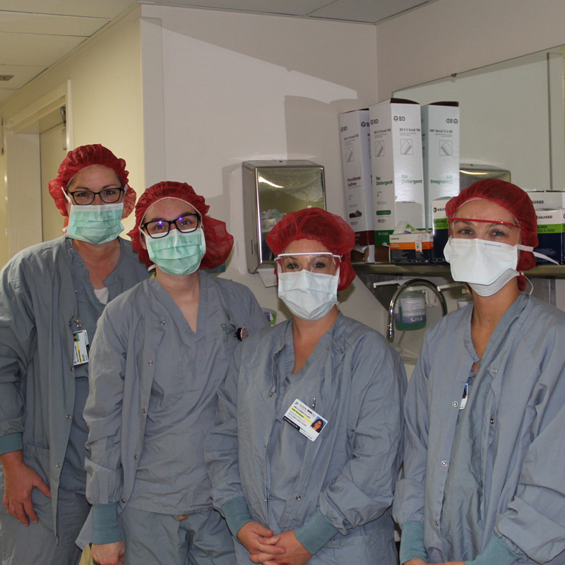 four students in scrubs and masks on