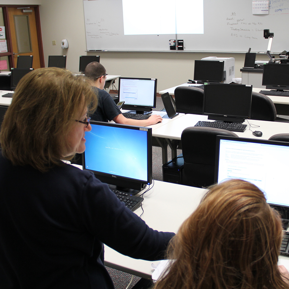 instructor helping a student on the computer
