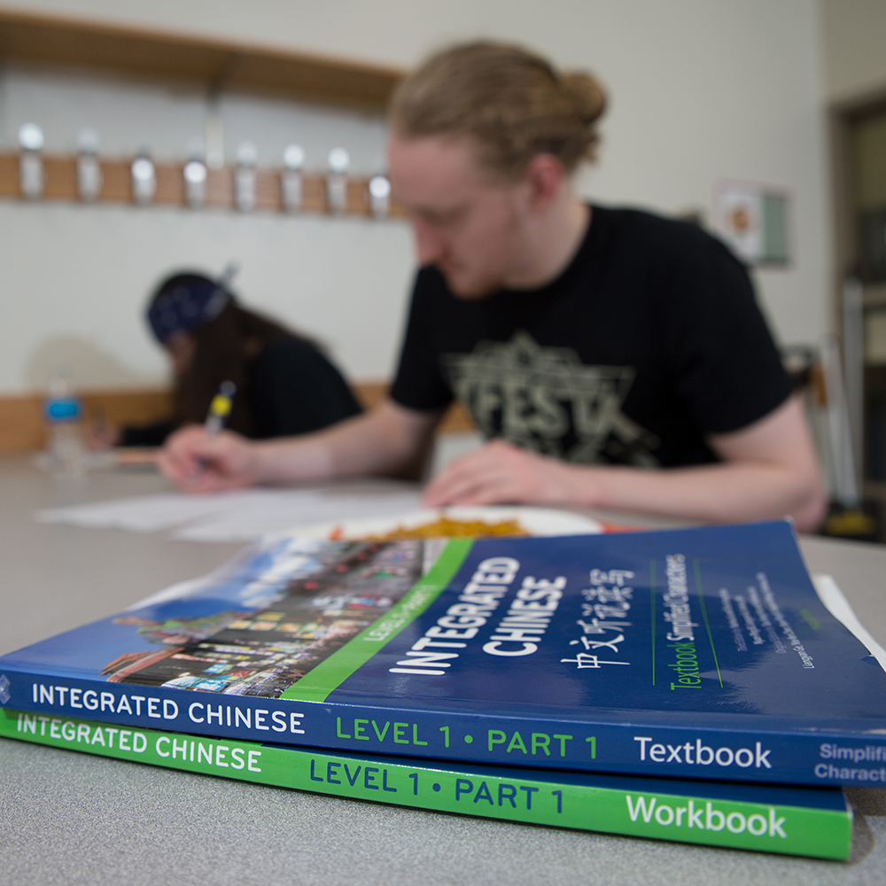 two college books on desk in front of student