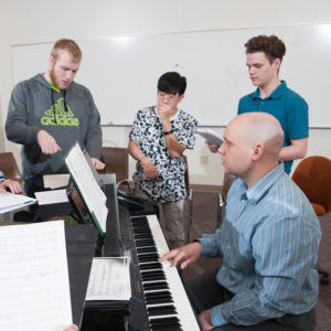 Students practice with instructor Steven Soebbing on the piano