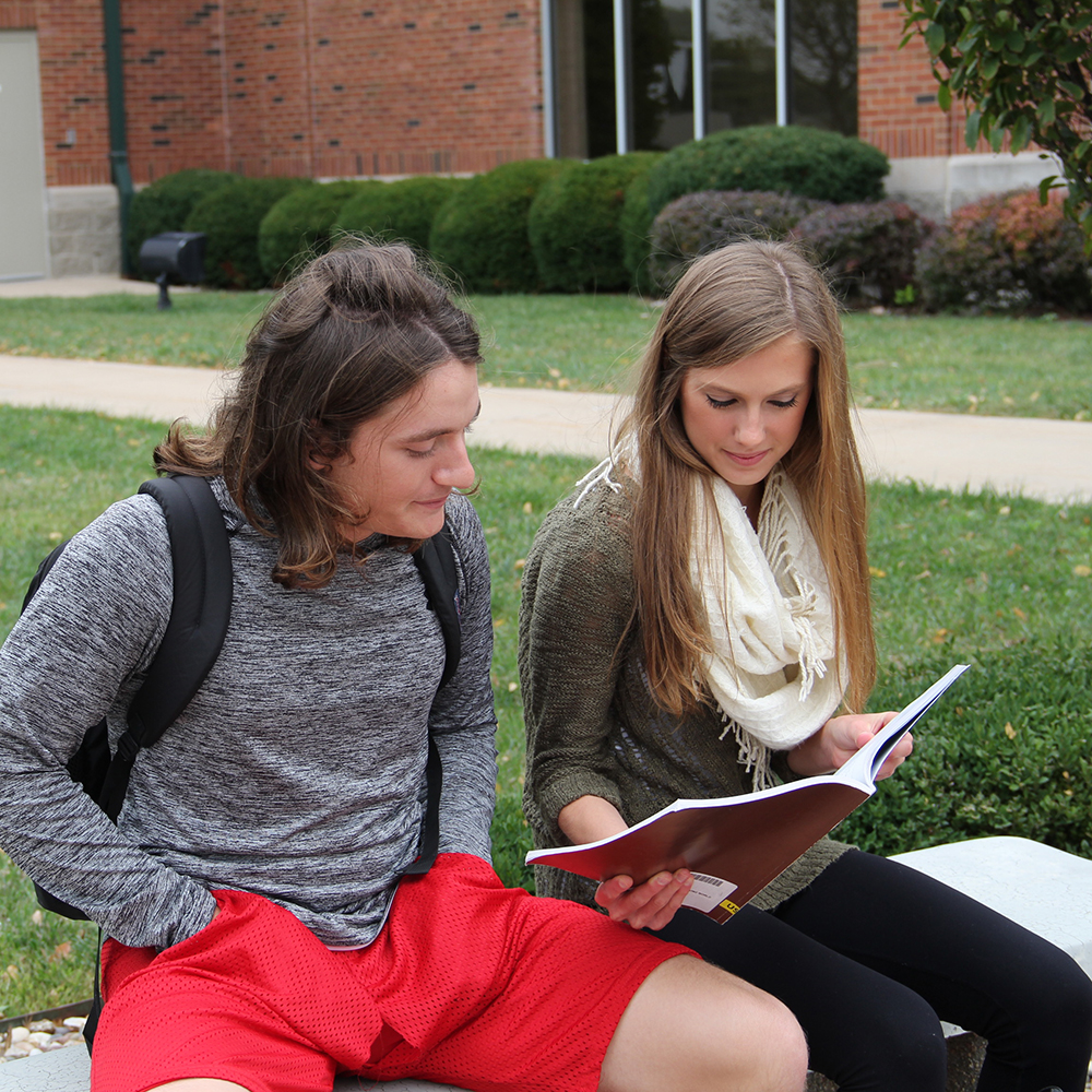 two students looking at a college book