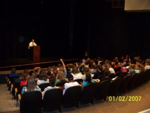 Many students listen to a speaker in an auditorium