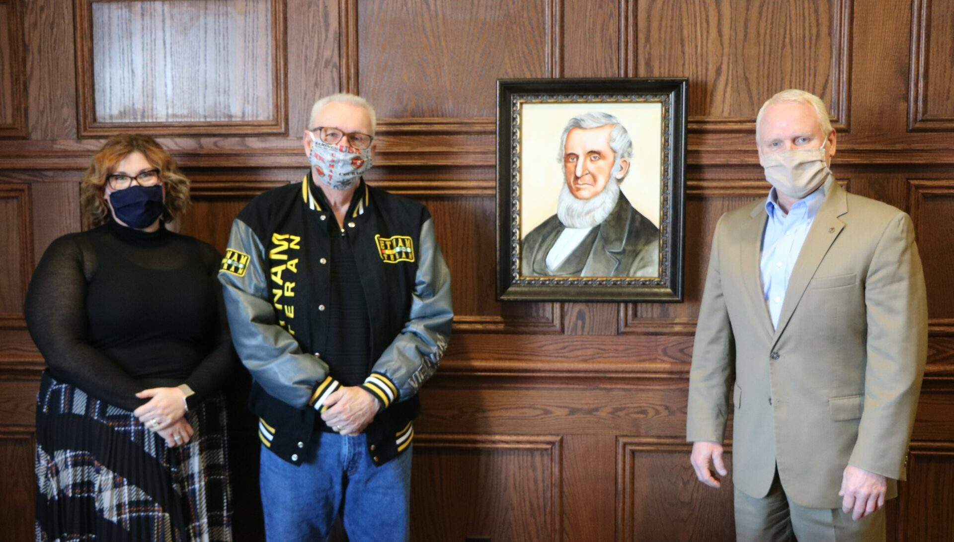 Dan Waggoner poses with his portrait of John Wood. the man