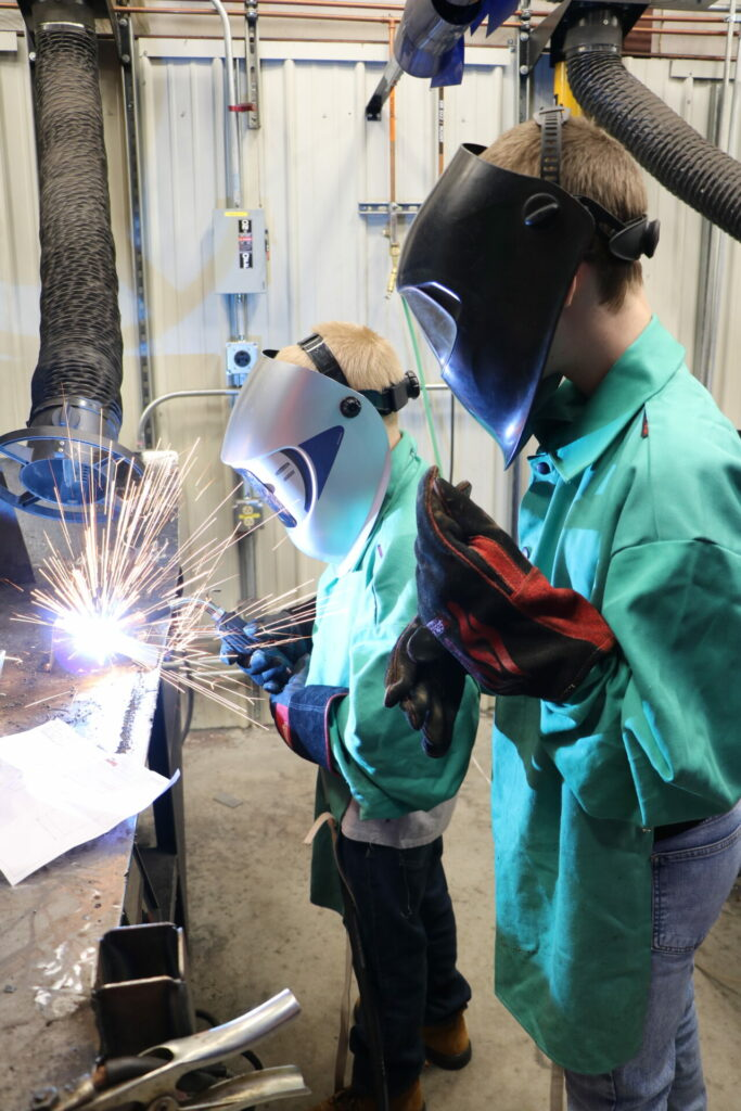 Young students wearing protective gear practice welding