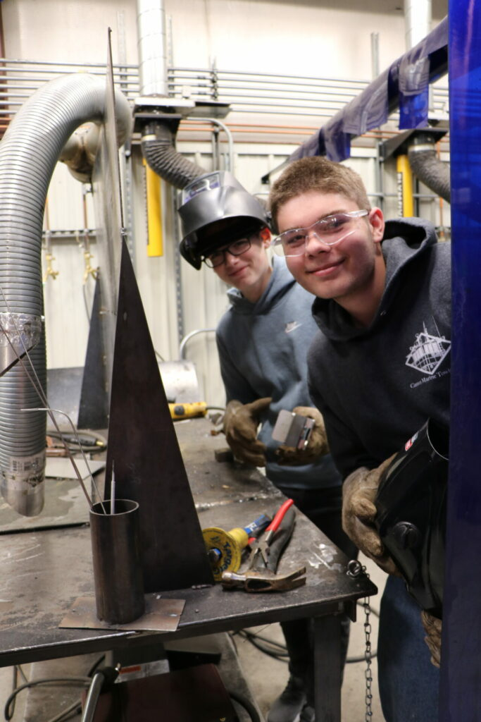 Two smiling students at a welding workstation