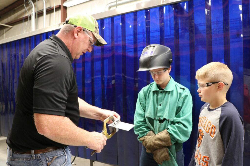 Welding instructor shows children equipment